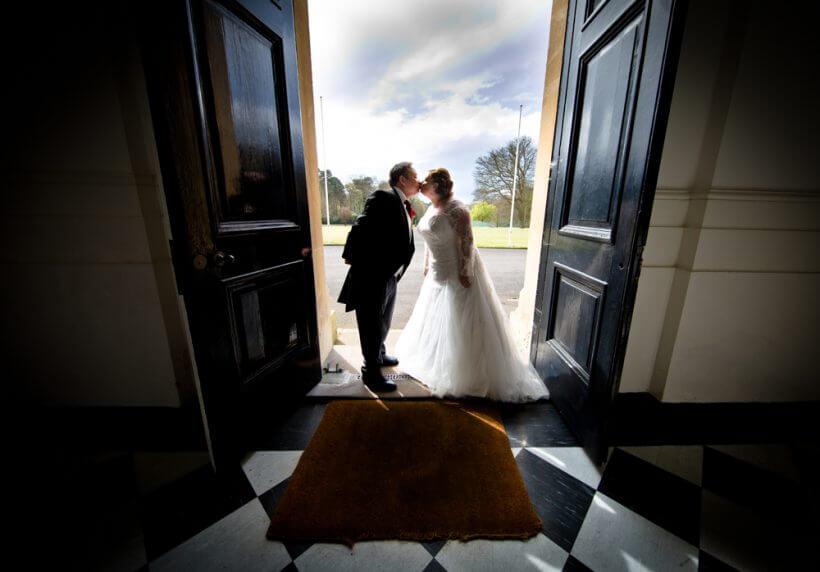 bride groom kiss kissing door way entrance