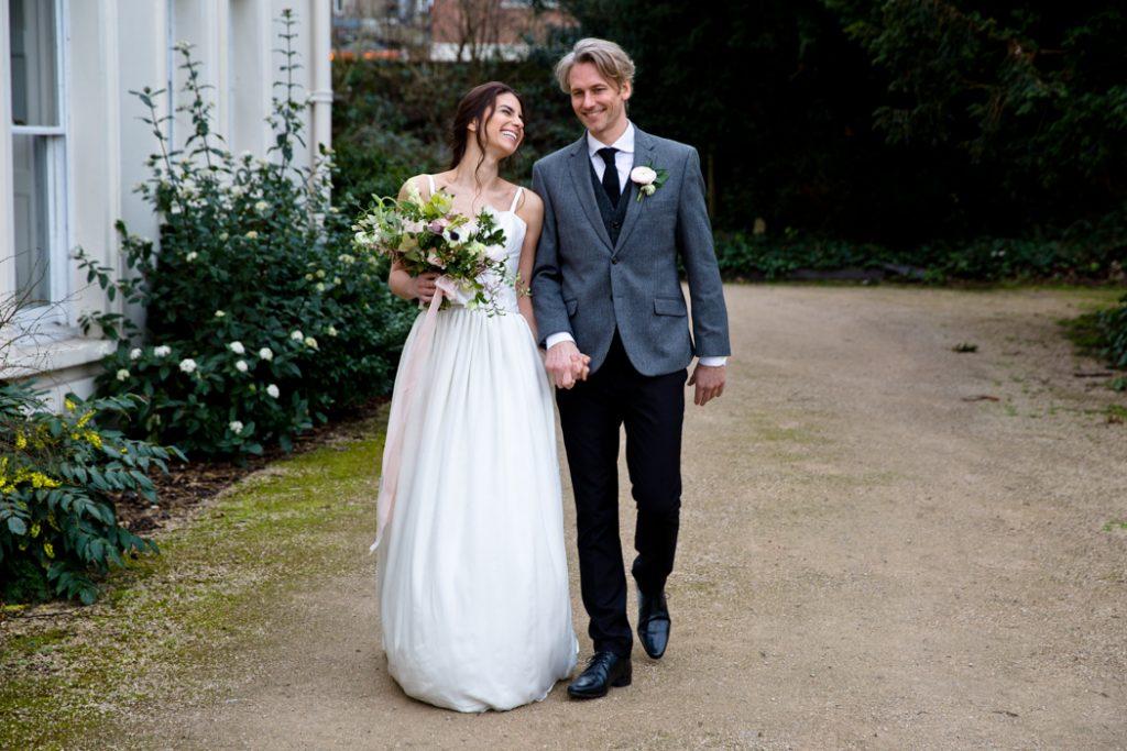 wedding dress bride groom walking flowers bouquet