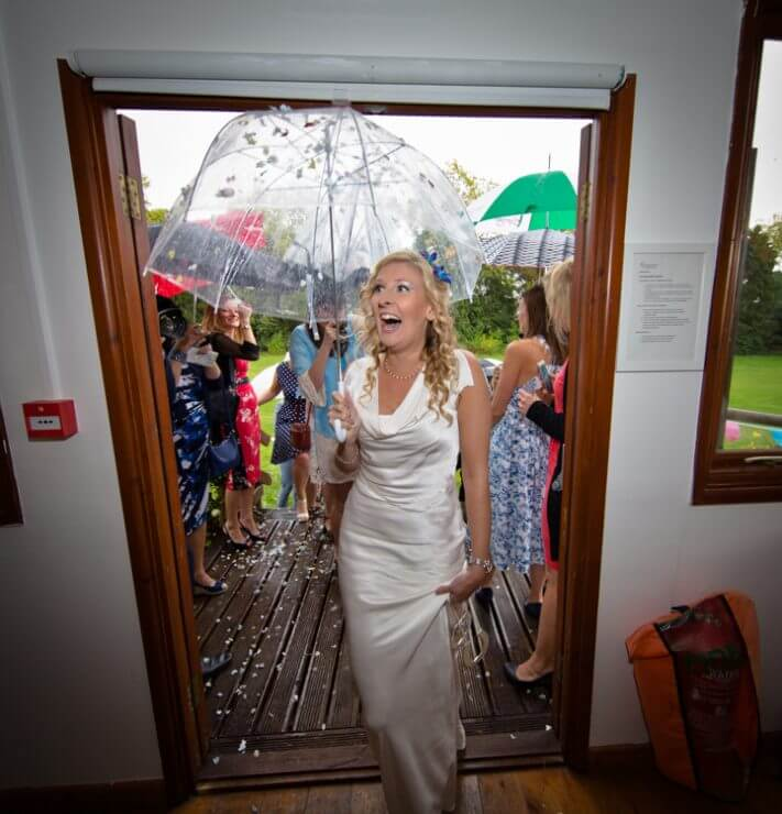 bride guests umbrella rain venue